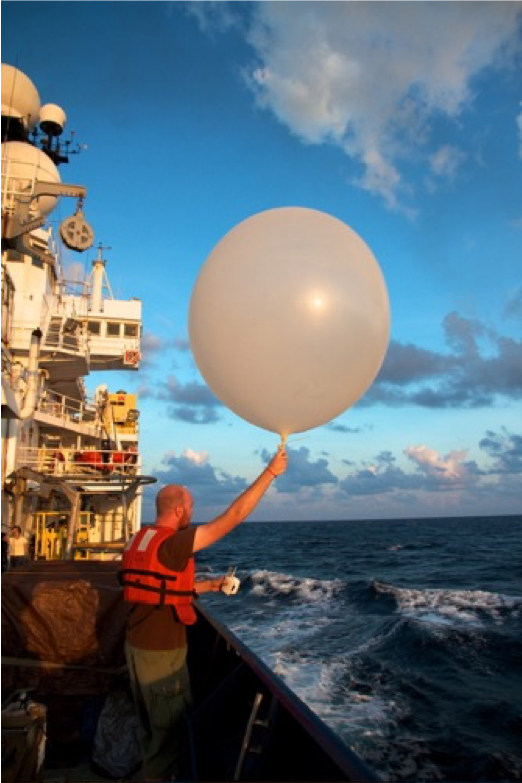 A researcher launches a radiosonde instrument attached to a weather balloon to capture detailed atmospheric data.