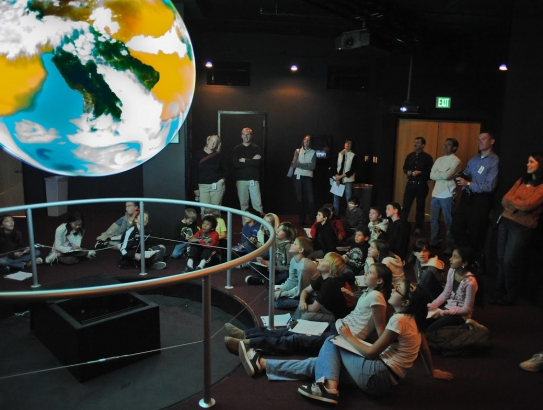 Students gather around Science on a Sphere, an educational tool that displays and animates Earth data on a globe. The Climate Education and Literacy Initiative will harness innovative approaches like this one to build awareness and understanding among the