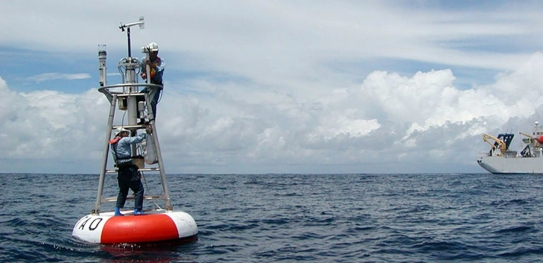 Technicians work on a NOAA buoy equipped with carbon dioxide sensors. Autonomous sensors like these have improved estimations of how much carbon is stored annually by the oceans. (Source: NOAA)